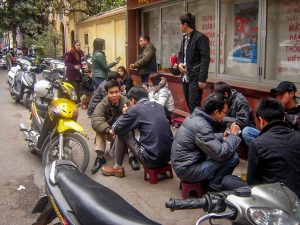 Улично заведение за бързо хранене в Ханой, Виетнам, с типичните насядали по малки столчета и масички хора.