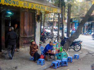 Типични търговци в Ханой, Виетнам, седящи на улицата на малки столчета в Ханой, Виетнам